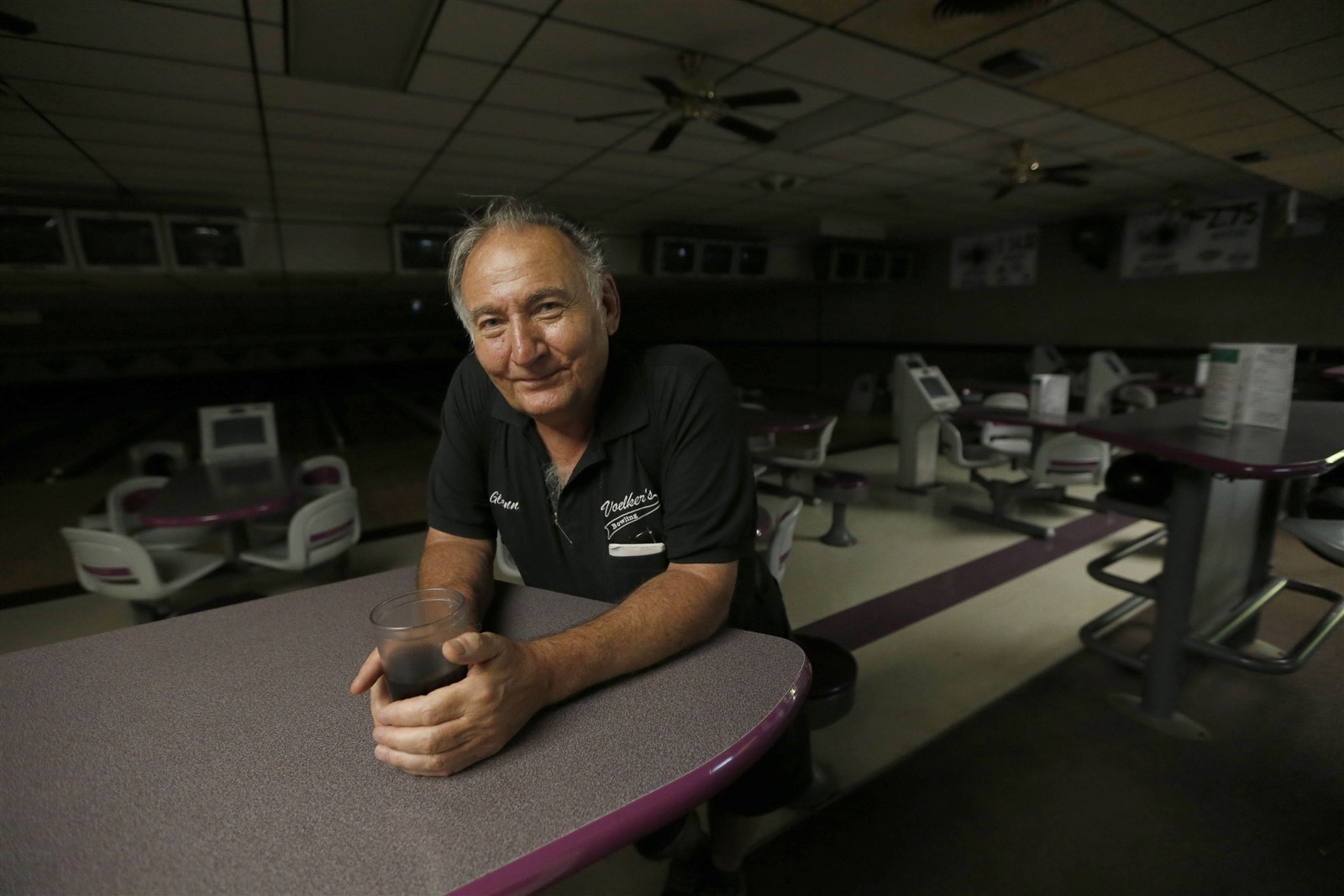 Glenn Voelker with his signature glass of black coffee in the bowling alley section of his family's establishment. He greets customers with a smile.